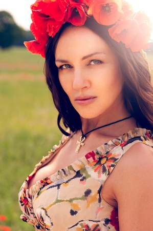 chaplet: Beautiful young brunette girl wearing flower chaplet in summer filed