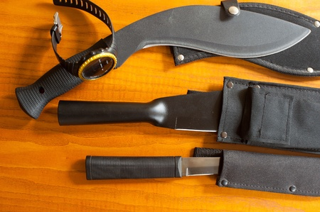 shrugged: Military knives and scabbard isolated on the wooden background