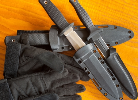 shrugged: Military knives and scabbard on the wooden background
