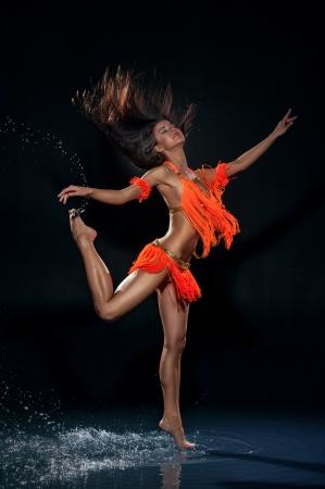 Dansende vrouw onder regen in oranje jurk Studio