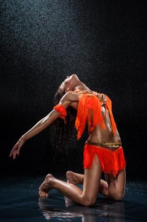 Frau tanzen unter regen in orange Kleid Studio