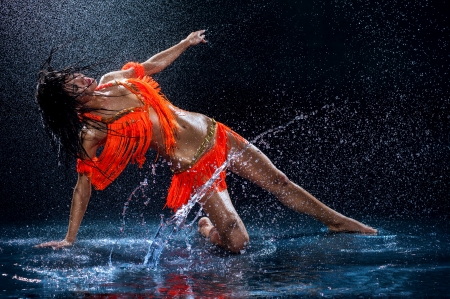 rain water: Woman dancing under rain in orange dress  Studio