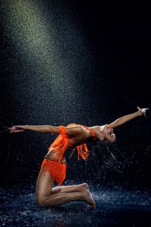 Woman dancing under rain in orange dress  Studio