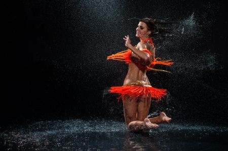 Woman dancing under rain in orange dress  Studio photo