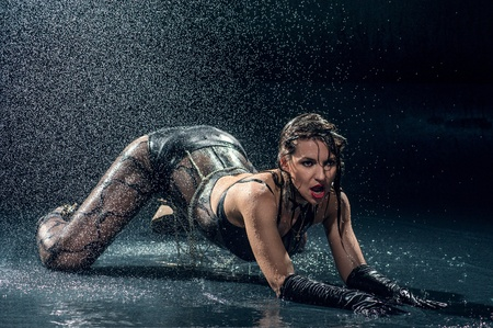 Wet woman in underwear dancing in a studio photo