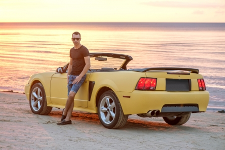 Man standing by his yellow sport car on sunset photo