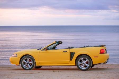 Yellow sport car at sunset near sea Stock Photo