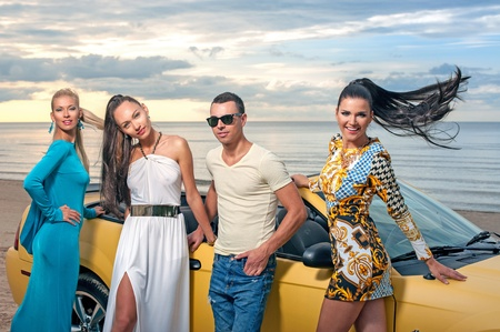 Three girls and a man with sport car on a sunset beach photo