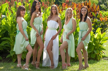 Group of happy Girls in summer dresses posing in park Stock Photo