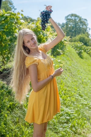 Portrait of a beautiful young blonde with a bunch of grapes photo