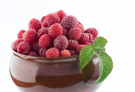 Big clay pot with fresh red raspberries photo