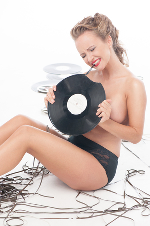 Sexy naked girl covered up with vinyl disc photo