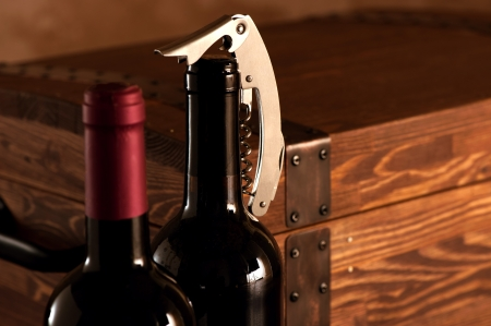 Wooden case with two bottles of red wine with corkscrew photo