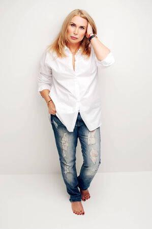 Lovely mature woman in white shirt and blue jeans photo