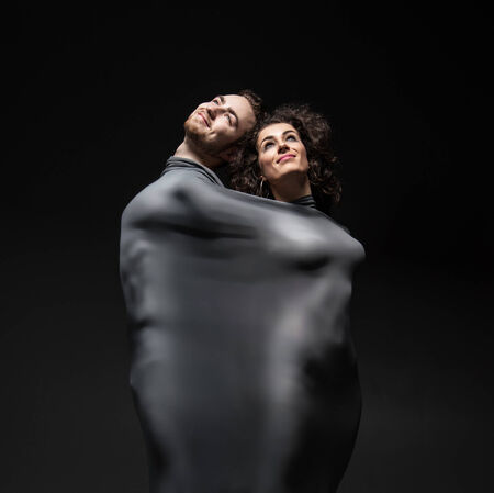 Silhouettes of man and woman wrapped in black cloth over dark background photo