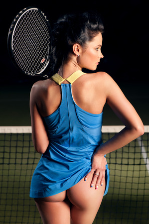 Beautiful girl on the tennis court with racket in hand photo