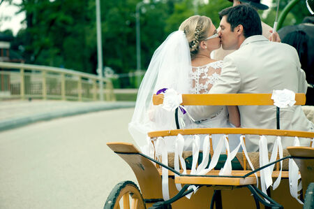 Romantic Bride and groom kissing in carriage on wedding day photo