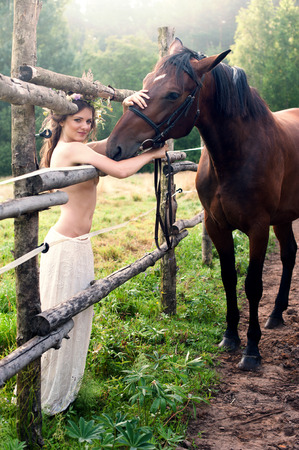 Young pretty brunette woman with horse near wooden fence photo