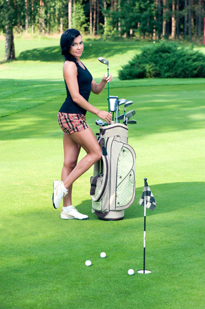 Sexy femail golfer with golf equipment photo