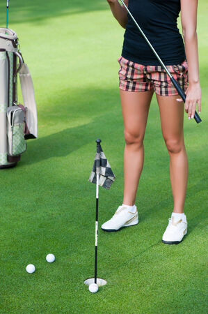 Attractive golfer girl on golf course photo