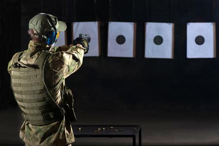 Man shooting with gun at a target in shooting range Standard-Bild