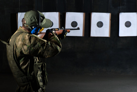 Man shooting with rifle at a target in shooting range Stock Photo