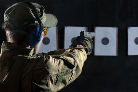 hombre disparando: Hombre de tiro con pistola a un blanco en campo de tiro Foto de archivo