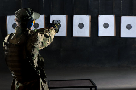 Man shooting with gun at a target in shooting range Stock Photo