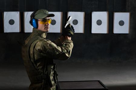 Man shooting with gun at a target in shooting range photo