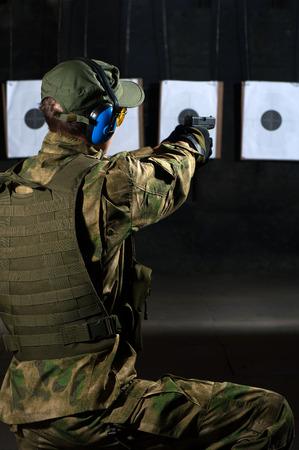 hombre disparando: Hombre disparando con el rifle a un blanco en campo de tiro