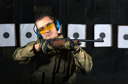 sniper training: Man shooting with rifle at a target in shooting range Stock Photo