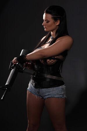 croft: Girl with machine gun on dark background