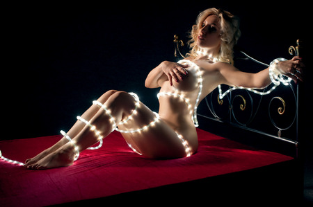 Nude woman with fairy lights laying on bed in darkness Stock Photo