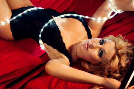 Woman in black lingerie with fairy lights laying on bed in darkness