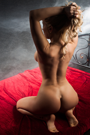 Nude woman back view on red bed