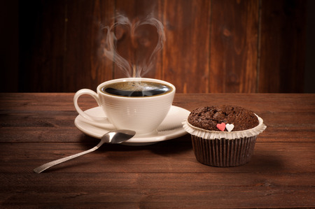 Delicious tasty cupcake and coffe cup on wooden table Stock Photo
