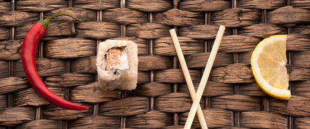 makki: Roll sushi, chopsticks, lemon and red peppers on wooden in word love
