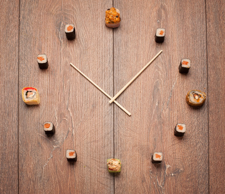 sushi: Sushi time in the form of a wall clock on a wooden background