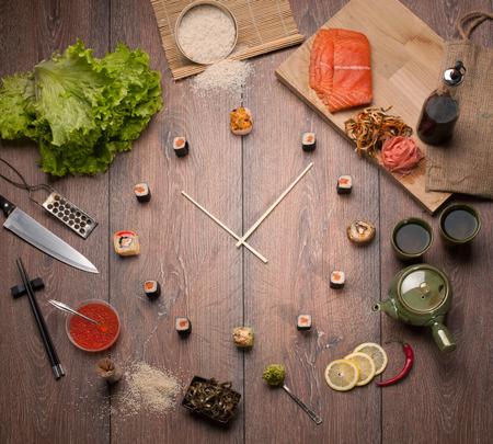 japanese sake: Tiempo del sushi en forma de un reloj de pared en un fondo de madera Foto de archivo