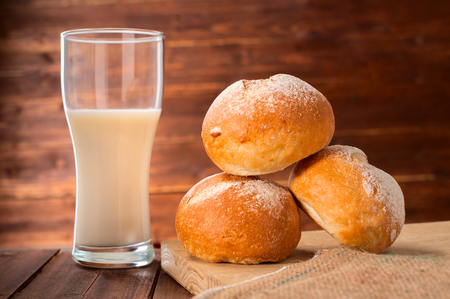 homemade bread: Freshly baked buns and glass of milk on wooden board