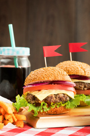 Tasty burgers with flags, french fries and beverage on wooden board photo
