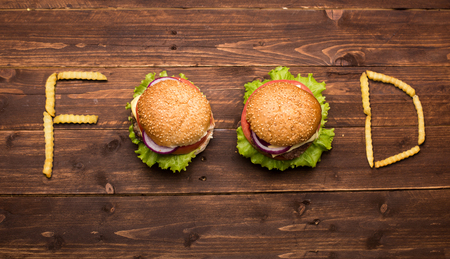 Tasty big burgers with french fries forming word food on wooden background photo
