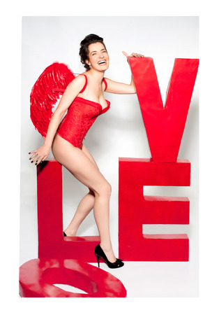 Female cupid in red corset with love word inscription Stock Photo