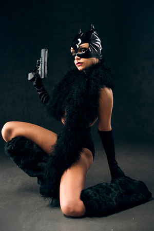 Sexy female in black catwoman costume with gun photo