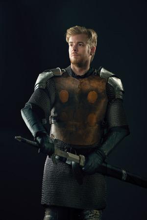 caballero medieval: Caballero antiguo en una armadura de metal con la espada sobre fondo gris Foto de archivo
