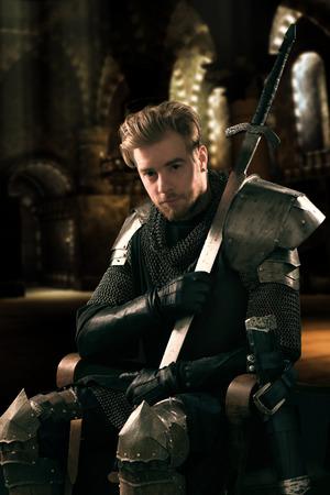 espadas medievales: Caballero antiguo en una armadura de metal que se sienta en una silla de madera en un palacio Foto de archivo