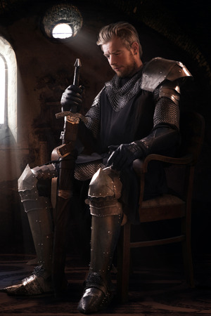 Ancient knight in metal armor sitting on a wooden chair in a palace