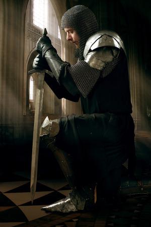 espadas medievales: Caballero antiguo en una armadura de metal con la espada de pie sobre una rodilla en un palacio