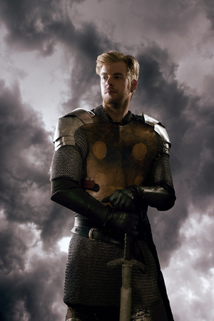 Ancient knight in metal armor with sword standing on a cloudy background Stock Photo