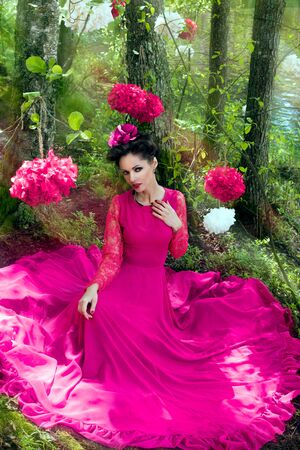 fairy woman: Young beautiful woman in long pink dress in the forest with decorative flowers